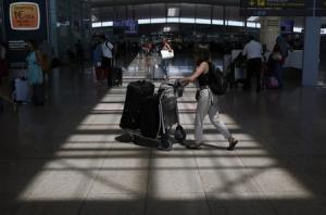 A woman pushes a trolley with suitcases at Barcelona's airport