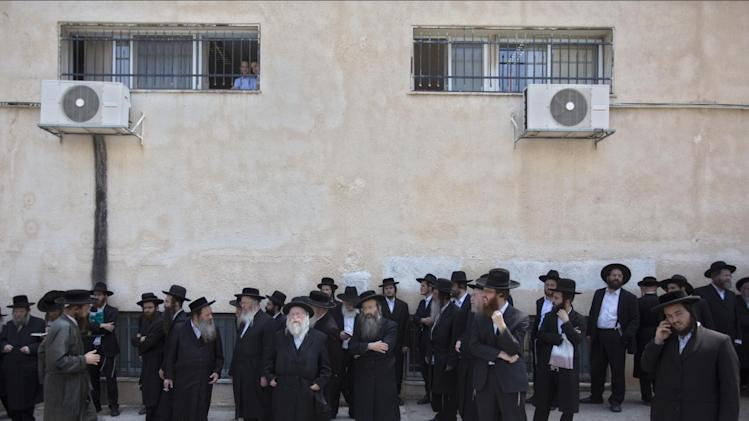 Ultra-Orthodox Jewish men pray during a protest against the decision to draft the ultra-Orthodox into military service in Jerusalem, Sunday, Aug. 31, 2014. (AP Photo/Sebastian Scheiner)