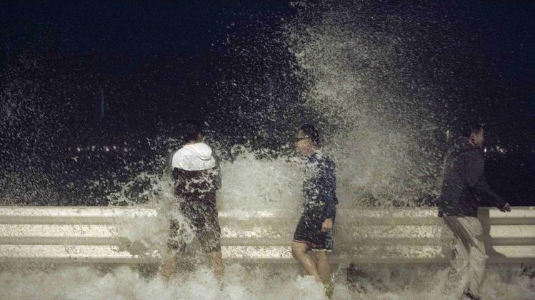 People react as waves splash on to the road during Typhoon Usagi in Hong Kong