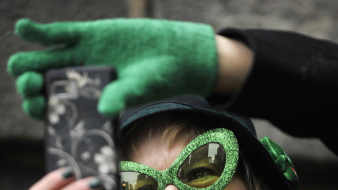 Patricia Dunne of Detroit, Mi. photographs The Chicago River being dyed green ahead of the St. Patrick's Day parade in Chicago, Saturday, March, 16, 2013. (AP Photo/Paul Beaty)
