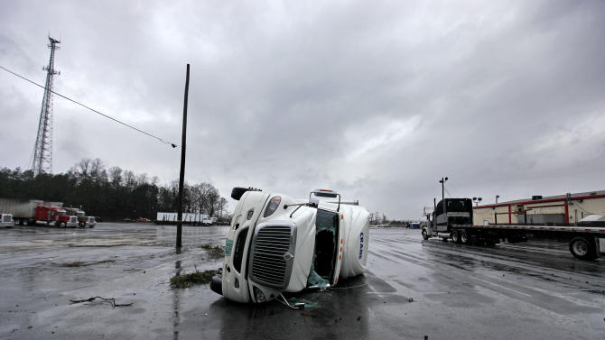 An overturned tractor trailer sits in a parking lot following a tornado, Wednesday, Jan. 30, 2013, in Adairsville, Ga. A fierce storm system that roared across Georgia has left at least one person dead after it demolished buildings and flipped vehicles on Interstate 75 northwest of Atlanta. (AP Photo/David Goldman)