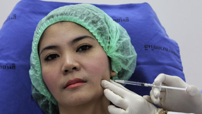 In this Oct. 17, 2012 photo, a 32-year-old Thai woman, Nisakron Boonpun gets a Botox injection at Bangkok's Yanhee Hospital, which houses one of the country's best-known and largest beauty clinics. Bangkok has more than 500 licensed beauty clinics that cater to the wealthy but is also full of illegal, back-alley beauticians who are attracting young and working-class customers with rock-bottom prices. The recent case of a 33-year-old aspiring model who died from a botched collagen injection has drawn attention to the dark side of a booming beauty industry in Thailand. (AP Photo/Sakchai Lalit)