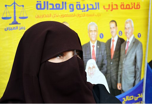 An Egyptian woman stands in front of a campaign banner in Arabic that reads,