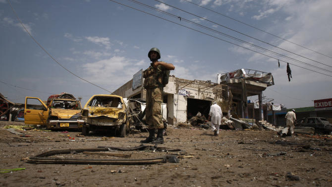 A Pakistan army soldier examines the site of a car bombing on the outskirts of Peshawar, Pakistan, Sunday, June 2013. the car bomb exploded as a convoy of paramilitary troops passed through the outskirts of the northwest Pakistani city of Peshawar, killing more than a dozen people and wounding scores of others, police said. (AP Photo/Mohammad Sajjad)