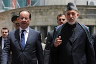 French President Francois Hollande (left) and Afghan president Hamid Karzai meet at the presidential palace in Kabul. Hollande has defended France's imminent exit from Afghanistan, saying 2,000 combat troops will leave in a coordinated withdrawal this year but vowing not to abandon the country