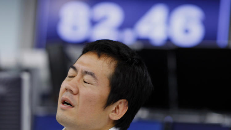 A money trader reacts during the morning trading at a brokerage in Tokyo Thursday, Nov. 22, 2012. In currencies, the euro rose to $1.2859 from $1.2825 late Wednesday in New York. The dollar slipped to 82.73 yen from 82.49 yen. (AP Photo/Junji Kurokawa)