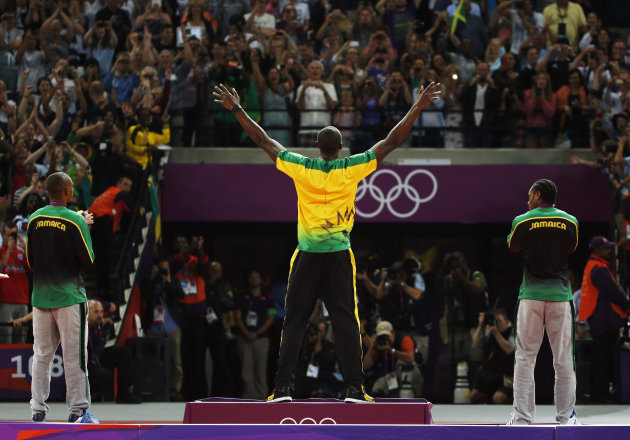 Jamaica's Usain Bolt, center, celebrates before receiving his gold medal as he stands alongside silver medallist Yohan Blake of Jamaica, right, and bronze medallist Warren Weir of Jamaica during the m