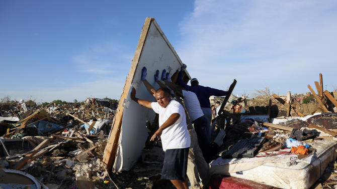 Men lift a wall in an effort to salvage belongings from their tornado-ravaged homes in Moore