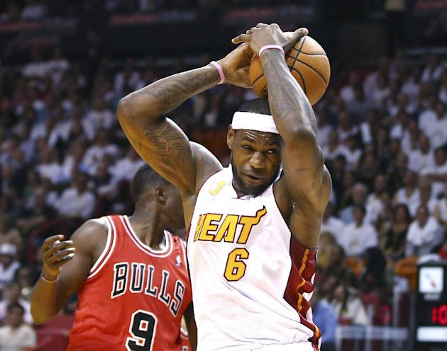 Miami Heat's LeBron James (6) loses control of the ball as Chicago Bulls' Luol Deng (9) defends during the first period of an NBA basketball game in Miami, Tuesday, Oct. 29, 2013