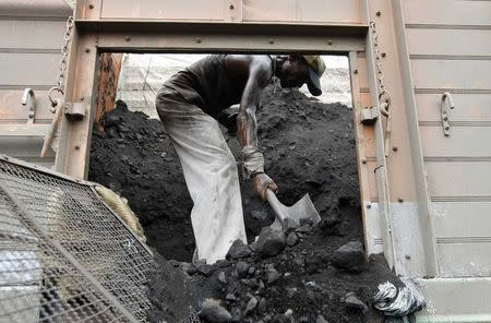 File photo of a labourer unloading coal from a supply truck at a yard on outskirts of western Indian city of Ahmedabad