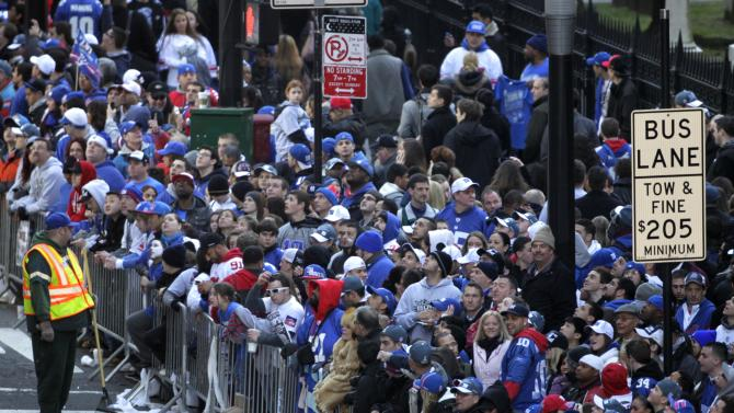 Fans line the streets in lower Manhattan waiting for the start of the New York Giants Superbowl parade in New York, Tuesday, Feb. 7, 2012. Eli Manning and the New York Giants are Super Bowl champions again. Just as they did four years ago in Arizona, Tom Coughlin's Giants have defeated Bill Belichick's New England Patriots, this time 21-17 in Indianapolis for their fourth Lombardi Trophy. (AP Photo/Seth Wenig)