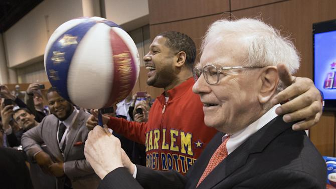 """Berkshire Hathaway Chairman and CEO Warren Buffett, right, is watched by Detroit Lions defensive tackle Ndamukong Suh, left, as he is assisted by Harlem Globetrotter Chris """"Handles"""" Franklin in spinning a basketball in Omaha, Neb., Saturday, May 4, 2013, before holding the Berkshire Hathaway shareholders meeting. Tens of thousands attend Berkshire Hathaway shareholder meeting to hear Warren Buffett and Charlie Munger answer questions for more than six hours. No other annual meeting can rival Berkshire's, which is known for its size, the straight talk Buffett and Munger offer and the sales records shareholders set while buying Berkshire products. (AP Photo/Nati Harnik)"""