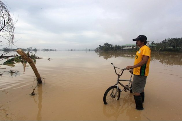 This picture taken on December 5, 2012 shows a man with his bicycle standing in a flooded street in the aftermath of Typhoon Bopha in New Bataan, Compostela Valley in the southern Philippines.