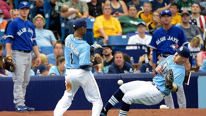 Tampa Bay Rays left fielder Brandon Guyer, right, drops a pop fly hit foul by Toronto Blue Jays' Dalton Pompey as shortstop Tim Beckham (1) watches during the eighth inning of a baseball game in St. Petersburg, Fla., Sunday, April 26, 2015. (AP Photo/Phelan M. Ebenhack)