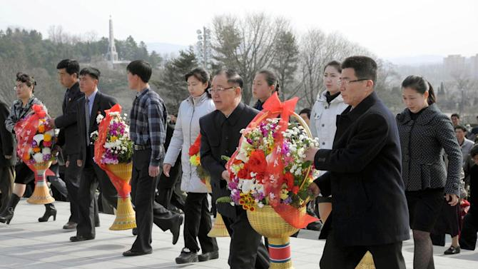 North Koreans carry flowers to giant statues of North Korean late leaders Kim Il Sung and Kim Jong Il at Mansu Hill in Pyongyang, North Korea, Monday, April 15, 2013. North Korea celebrated Monday the 101st birth anniversary of national founder Kim Il Sung, its most important holiday of the year. (AP Photo/Kyodo News)  JAPAN OUT, MANDATORY CREDIT, NO LICENSING IN CHINA, HONG KONG, JAPAN, SOUTH KOREA AND FRANCE