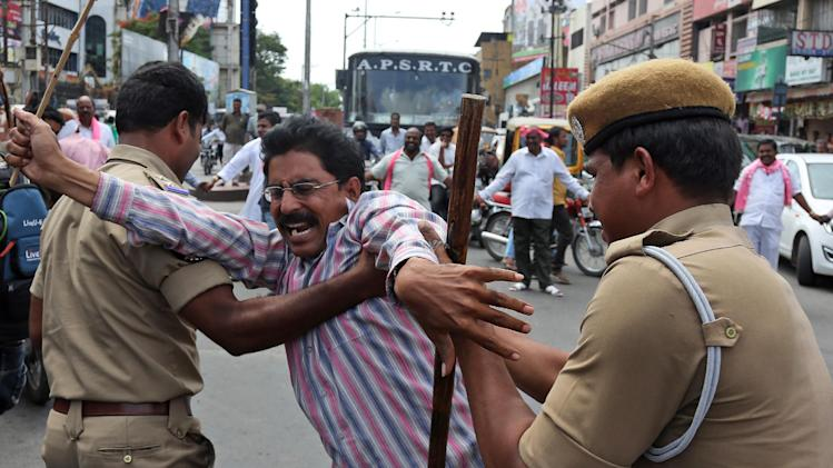Indian policemen detain an activists protesting against the ordinance on Polavaram project in Hyderabad, India, Saturday, July 12, 2014. A day-long strike has been called in Telangana state to protest the ordinance under which more than 100 villages of Telangana state will be transferred to Seemandhra state to aid the construction of the irrigation project. (AP Photo/Mahesh Kumar A.)