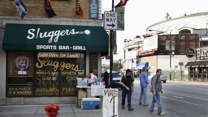 FILE - In this Sept. 21, 2010 file photo, patrons walk near a bar near Wrigley Field, seen at right background, in Chicago. On Monday, April 23, 2012, Sami Samir Hassoun, a Lebanese immigrant accused of of placing a backpack he thought held a bomb near the bar and home of the Chicago Cubs, pleaded guilty to weapons charges at federal court in Chicago and could face up to 30 years in federal prison. (AP Photo/Charles Rex Arbogast, File)