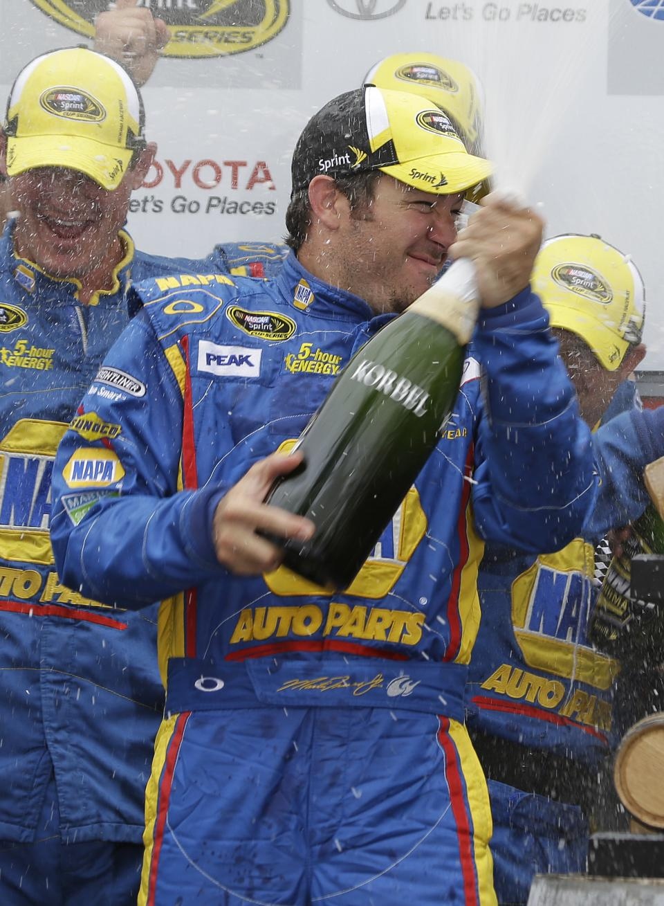 Martin Truex Jr. sprays his team after winning the NASCAR Sprint Cup series auto race on Sunday, June 23, 2013, in Sonoma, Calif. (AP Photo/Eric Risberg)