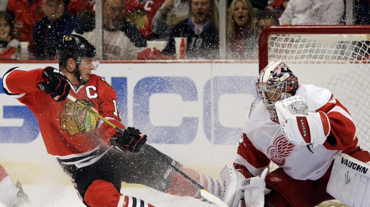 Detroit Red Wings goalie Jimmy Howard, right, saves a shot by Chicago Blackhawks' Jonathan Toews, left, during the second period of Game 5 of the NHL hockey Stanley Cup playoffs Western Conference semifinals in Chicago, Saturday, May 25, 2013. (AP Photo/Nam Y. Huh)