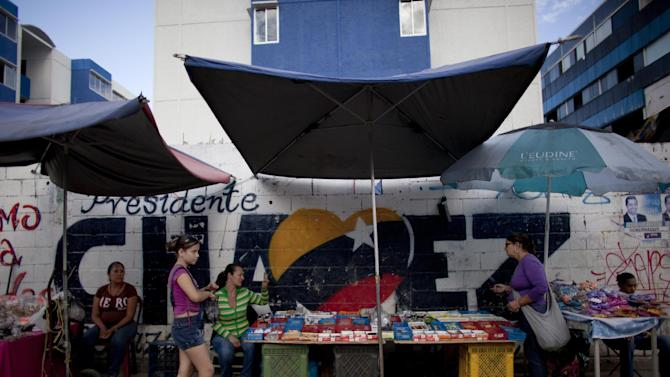 """Street vendors work in front of a mural that reads """"Chavez"""" regarding to Venezuela's president Hugo Chavez in Caracas, Venezuela, Tuesday, Dec. 18, 2012. Chavez is recovering in Cuba from a surgery, his fourth operation related to his pelvic cancer since June 2011. (AP Photo/Ariana Cubillos)"""