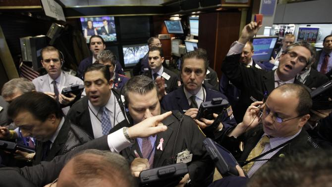 """Traders gather at the post that handles shares of NYSE Euronext as they wait for trading to resume, on the floor of the New York Stock Exchange, Wednesday, Feb. 9, 2011. Stock market operator NYSE Euronext confirms it's in """"advanced discussions"""" about a potential business combination with Germany's Deutsche Boerse AG. (AP Photo)"""