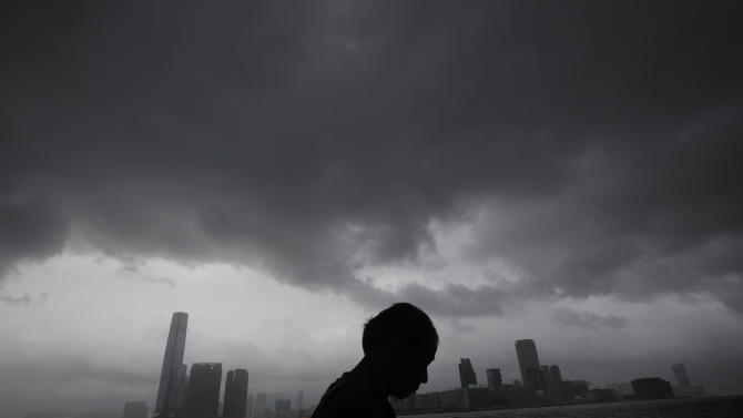 A man walks at a pier against a backdrop of Hong Kong's Victoria Habour Thursday, Sept. 29, 2011. Residents of Hong Kong hunkered down Thursday as they rode out a powerful typhoon that brought death and destruction when it tore through the Philippines earlier this week. Hong Kong's stock market suspended trading and shops and businesses shuttered as Typhoon Nesat made its way across the South China Sea from the Philippines, where the storm killed 35 people and that left another 45 missing. (AP Photo/Vincent Yu)
