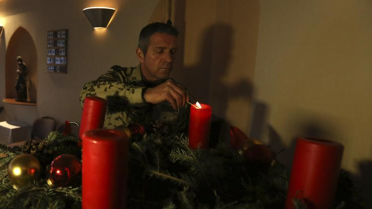 A German soldier lights a candle at a church in Mazar-i-Sharif