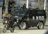 A Tibetan rides past an armoured police personnel carrier in China's northwest Qinghai, in March 2012. Hundreds of Tibetans demonstrated in northwest China on Tuesday after police beat four people, an exile group and a US broadcaster said, following a recent string of self-immolations in the region