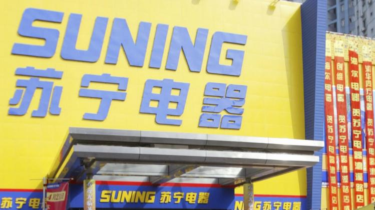 File picture of a man riding a tricycle in front of a Suning Appliance branch in Shanghai