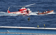 Italian firefighters are lowered from an helicopter onto the grounded cruise ship Costa Concordia off the Tuscan island of Giglio, Italy, Monday, Jan. 30, 2012. Residents of Giglio are growing increasingly worried about threats to the environment and the future of the Italian island as bad weather again forced suspension of the recovery operation of the capsized cruise ship Costa Concordia. (AP Photo/Pier Paolo Cito)