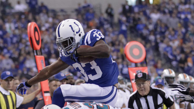 Indianapolis Colts running back Vick Ballard, top, tries to leap over Miami Dolphins cornerback Nolan Carroll during the first half of an NFL football game in Indianapolis, Sunday, Nov. 4, 2012. (AP Photo/AJ Mast)