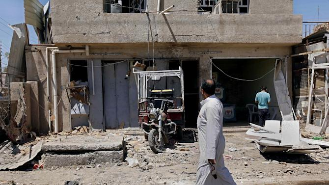 Civilians inspect the aftermath of a car bomb attack in the Husseiniyah area of northeastern Baghdad, Iraq, Thursday, April 25, 2013. A car bomb exploded after sunset on Wednesday, April 24, 2013 near a bus stop in Baghdad's mostly Shiite neighborhood of Husseiniyah, killing and wounding dozens of people, police said. (AP Photo/ Hadi Mizban)