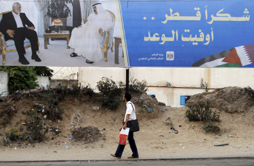 Palestinian youth walks near a poster of Gaza's Hamas Prime Minister Ismail Haniyeh, left, and Emir of Qatar Sheikh Hamad bin Khalifa al-Thani in Gaza City, Sunday, Oct. 21, 2012. The poster announces the coming visit  of the Emir of Qatar, it reads,
