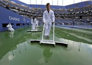 Court attendants dry center court at the US Open in New York as heavy rain delays the start of play