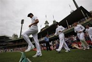 England's captain Alastair Cook (front) walks onto the ground with his team at the start of the first day of the fifth Ashes cricket test match against Australia in Sydney January 3, 2014. REUTERS/David Gray