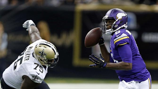 Minnesota Vikings quarterback Teddy Bridgewater (5) scrambles under pressure from New Orleans Saints defensive end Tyrunn Walker (75) in the second half of an NFL football game in New Orleans, Sunday, Sept. 21, 2014