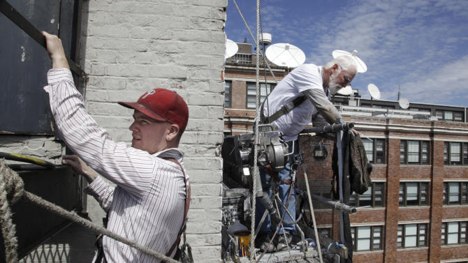 In this April 17, 2012 photo, apprentice billboard painter Liam McWilliams, left, works on a New York City wall as his mentor, Art Pastusak, makes an adjustment on the scaffolding. Pastusak, a billboard artist since 1977 has taken McWilliams, a 2010 graduate of Pratt University, as his apprentice in August 2011. Their nostalgic form of advertising is thriving again in New York City. (AP Photo/Bebeto Matthews)