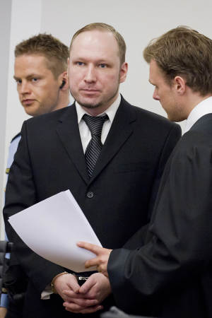 Defendant Anders Behring Breivik seen talking to one of his lawyers, Tord Jordet, right, during the fourth day of proceedings in the courthouse in Oslo, Norway, Thursday April 19, 2012.  Confessed mass killer Anders Behring Breivik testified Thursday that he had planned to capture and decapitate former Norwegian Prime Minister Gro Harlem Brundtland during his shooting massacre on Utoya island. (AP Photo / Erlend Aas)