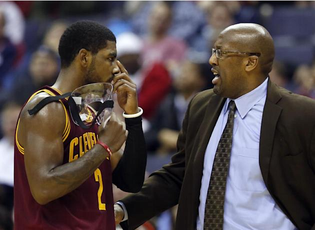 Cleveland Cavaliers guard Kyrie Irving (2) talks with head coach Mike Brown in the second period of an NBA basketball game against the Washington Wizards, Saturday, Nov. 16, 2013, in Washington. The C