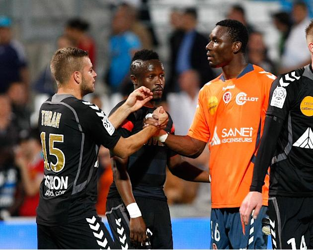 Stade de Reims' goalkeeper Kossi Agassa, center right, midfielder Bocundji Ca, center, and defender Atila Turan celebrate after defeating Marseille during their League One soccer match, at the Velodro