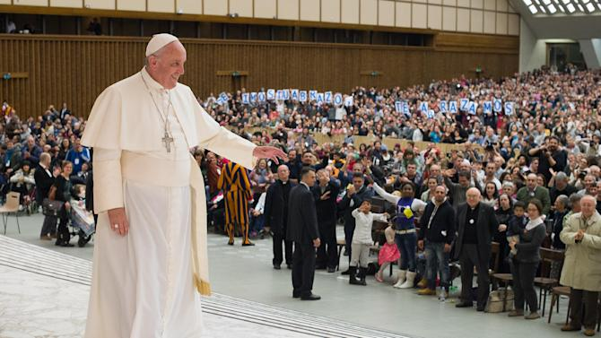Pope Francis waves to faithful during a meeting with members of Pope John XXIII Community in the Paul VI hall at the Vatican, Saturday, Dec. 20, 2014. (AP Photo/L'Osservatore Romano, ho)