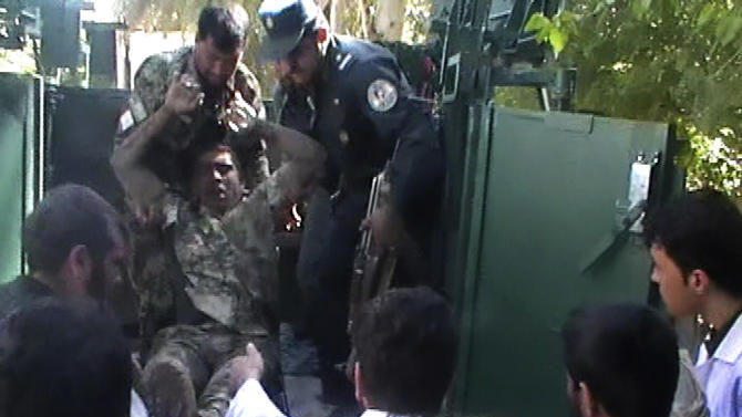 This image made from AP video shows an injured Afghan National Army soldier taken off from a military vehicle outside  the local hospital in Farah, western Afghanistan, Wednesday, April 3, 2013. Suicide bombers disguised as Afghan soldiers stormed a courthouse Wednesday in a failed bid to free more than a dozen Taliban prisoners in western Afghanistan, officials said. Scores of people, including the attackers were reported killed in the fighting. The assault in Farah province was the latest example of the Taliban's ability to strike official institutions despite tight security measures. (AP Photo via AP video)