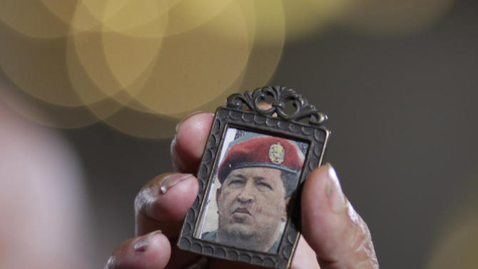 "A woman holds up an image of Venezuela's President Hugo Chavez as people gather to pray for him at a church in Caracas, Venezuela, Monday, Dec. 31, 2012. Venezuela's President Hugo Chavez is confronting ""new complications"" due to a respiratory infection nearly three weeks after undergoing cancer surgery, his Vice President Nicolas Maduro said Sunday evening in Cuba as he visited the ailing leader for the first time since his operation. (AP Photo/Ariana Cubillos)"