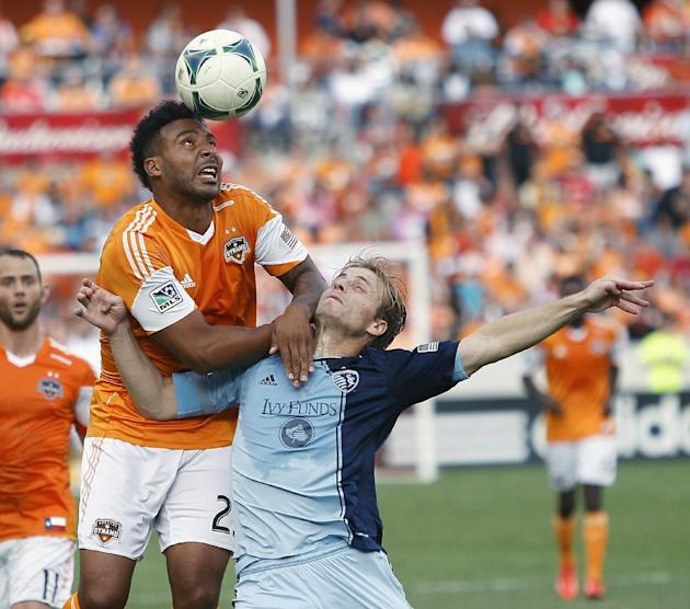 Houston Dynamo's Giles Barnes, left, heads the ball away from Sporting KC defender Seth Sinovic, right, during the second half of the MLS Eastern Conference soccer final on Saturday, Nov. 9, 2013, in
