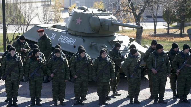 Pro-Russian separatists stand in formation in front of a Soviet World War Two T-34 tank, as they take an oath of loyalty to the separatist Interior ministry in Donetsk