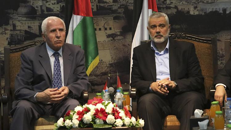 Gaza's Hamas Prime Minister Ismail Haniyeh, right, and senior Fatah official Azzam al-Ahmad meet in Gaza for talks aimed at reaching a reconciliation agreement between the two rival Palestinian groups, Hamas and Fatah on Tuesday, April 22, 2014. Palestinians have been divided since 2007 when Hamas took control of the Gaza Strip from Fatah forces loyal to Palestinian President Mahmoud Abbas. (AP Photo/Hatem Moussa)