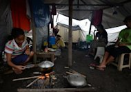 A resident and survivor of super Typhoon Haiyan prepares a meal inside a tent serving as a temporary shelter in Tacloban City, Leyte province, on December 25, 2013