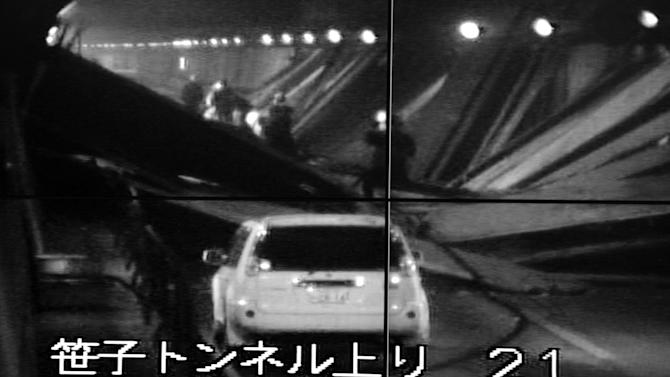 This image taken from the monitoring camera of Central Nippon Expressway's Hachioji branch, Tokyo, shows the fallen roof panels in the Sasago Tunnel, Yamanashi Prefecture, central Japan, Sunday, Dec. 2, 2012.  At least seven people were feared missing after parts of a tunnel collapsed Sunday on the highway west of Tokyo, trapping vehicles as smoke from a fire inside initially prevented rescuers from approaching.  The words at bottom read: Sasago Tunnel (To Tokyo).  (AP Photo/Kyodo News) JAPAN OUT, MANDATORY CREDIT, NO LICENSING IN CHINA, FRANCE, HONG KONG, JAPAN AND SOUTH KOREA