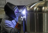 In this Dec. 14, 2011 photo, Kevin Offield makes a weld on a tank at JV Northwest, in Canby, Ore. JV Northwest manufactures stainless steel vessels. The number of people applying for unemployment benefits dropped to its lowest level since April 2008, continuing a downward trend that reflects a strengthening job market. (AP Photo/Rick Bowmer)