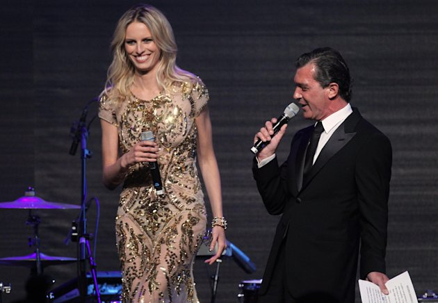 Karolina Kurkova and Antonio Banderas at the auction for the amfAR Cinema Against AIDS benefit during the 65th Cannes film festival, in Cap d'Antibes, southern France, Thursday, May 24, 2012. (AP Photo/Joel Ryan)